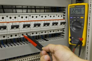 Electrical engineer measuring voltage on a miniature circuit breaker.
